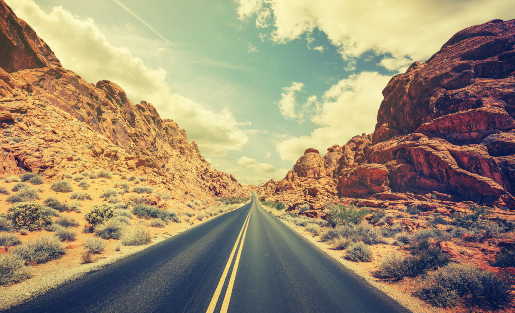The wide open road in the desert with mountains to the left and right