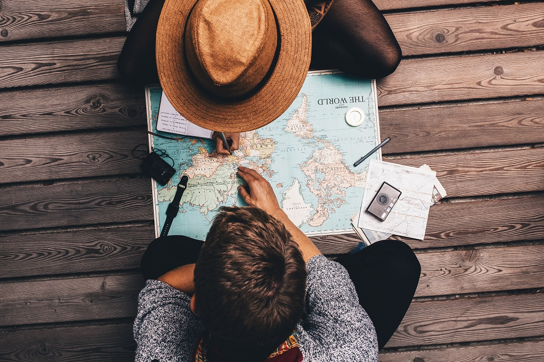 Man and woman making vacation plans using the world map. Couple sitting by the map and exploring it.